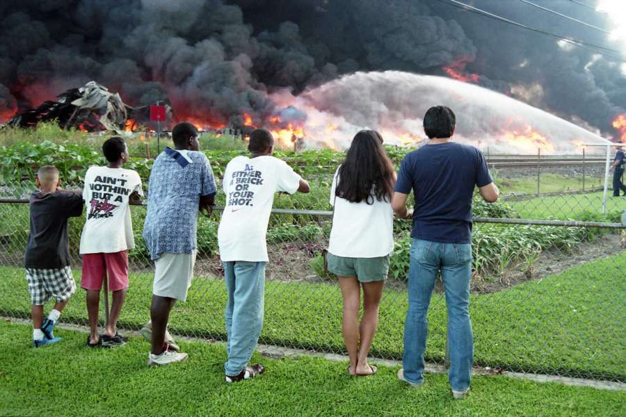 Image shows 6 residents of Pleasantville, including four young boys and an adult couple, standing beside a chain link fence watching firefighters send jets of water into the blaze. Between the watchers and the fire, there is what appears to be a community garden, then the railroad tracks are visible further in the distance. One firefighter is visible on the right-hand side of the image, next to the stream of water that is shooting into the flames. The fire is orange and yellow, close to the ground, with thick black clouds of smoke obscuring the entire sky in the picture. Image is in color, courtesy of Howard Castleberry for the Houston Chronicle, dated June 24, 1995.