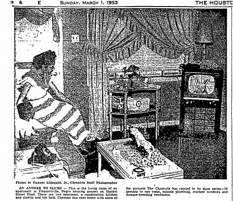 """The black and white photo shows a Black woman in her living room, sitting on a couch or bed watching television. The room is well furnished, with curtains, a lamp, a telephone, and various decorations and appliances in view. The image caption lists the features of a typical Pleasantville apartment, including two bedrooms, a combination kitchen and dinette, and a tile bath. Image courtesy of Gunnar Liljequist Jr. from the Houston Chronicle (""""An Answer to Slums"""") dated March 1, 1953."""