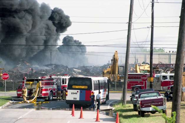 Image shows debris and rubble from the initial warehouse fires, with a cloud of dark grey smoke rising from it. In front of the destroyed warehouses, there are two fire trucks, a city bus, several trucks, and a piece of construction equipment. Several firefighters can be seen handling a hose in the back of one truck that has been used to combat the flames. Image is in color. Courtesy of Ben DeSoto for the Houston Chronicle, dated July 23, 1995.