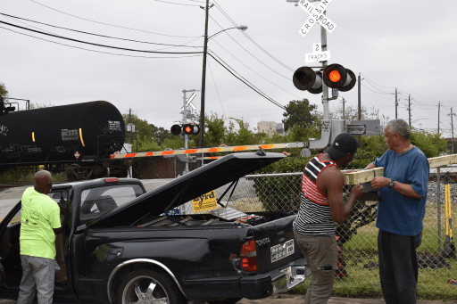 ACTS volunteers stand in front of a truck and railroad crossing as they install an air quality monitor nearby.