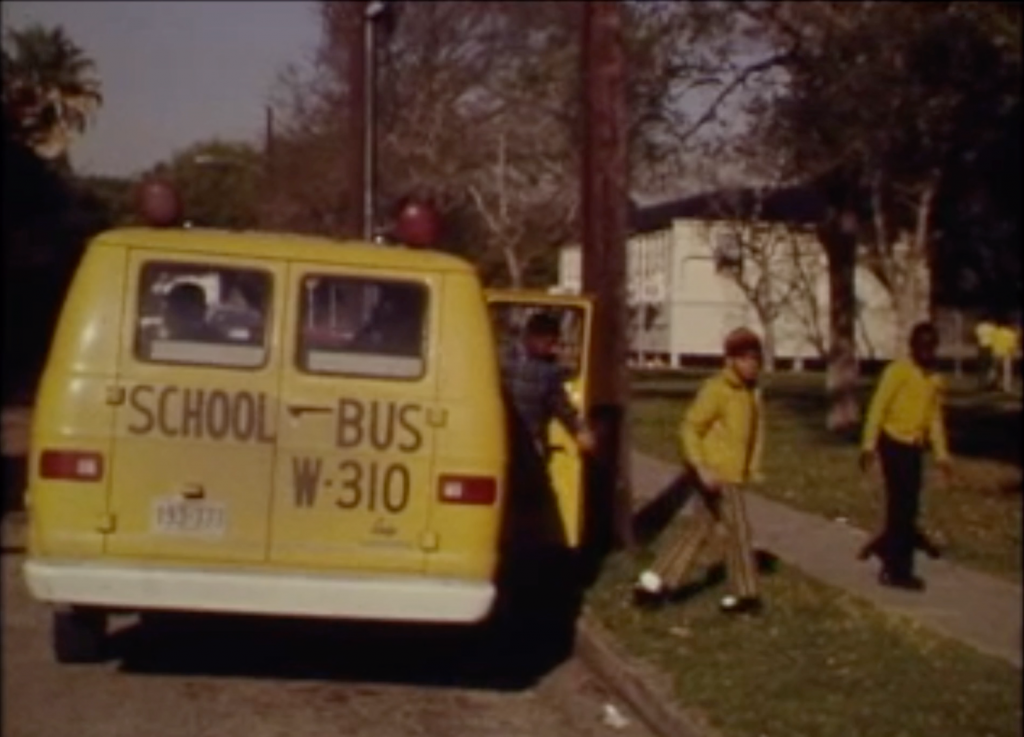 """This still from a 1972 newsreel shows a small yellow van-style school bus topped with red safety lights stopped at a greasy street. The back of the bus says """"School Bus W-310"""" in large black letters. Three Black boys are exiting the school bus."""