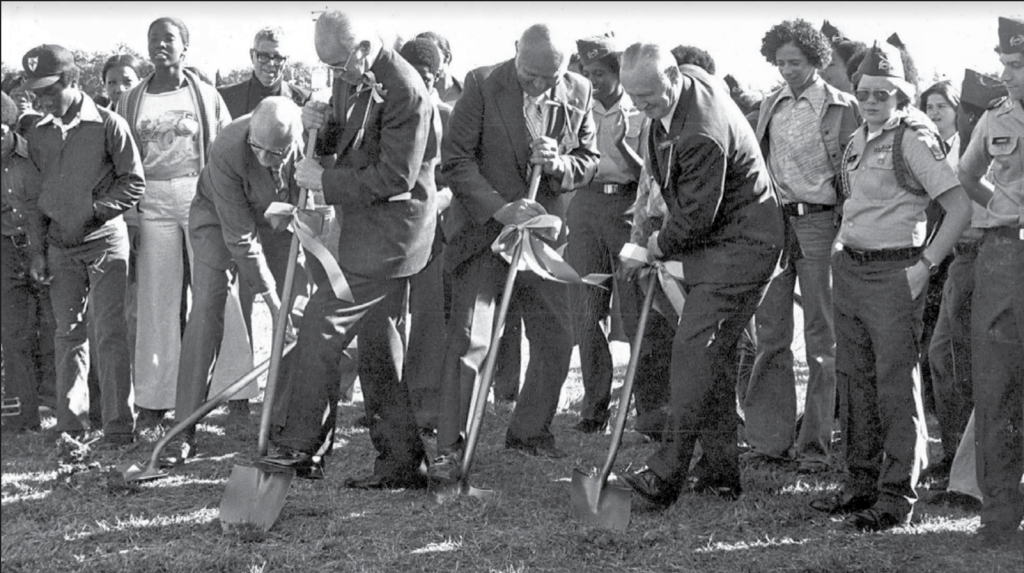 Black and white photograph of Black and white students and teachers gathered around four grey haired white men in suits, who smile while digging into the earth with shovels.