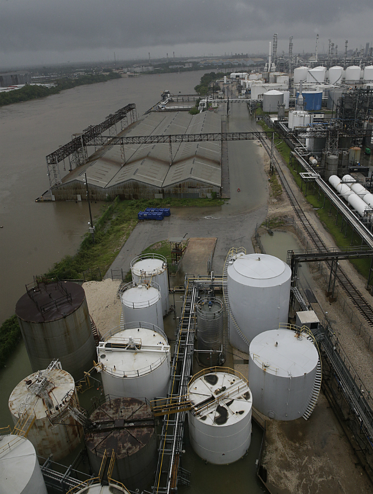 A high angle photograph shows large above ground chemical storage tanks, rows of low metal buildings with peaked roofs, railway lines, and a sprawling tangle of other chemical processing infrastructure that stretches to the horizon. The murky water of the Houston Ship Channel edges the scene on the left side, and is seeping onto the land. Water surrounds the low metal buildings and part of the rail line is submerged. The sky is grey, and a ceiling of low lying clouds is visible across the top of the image.